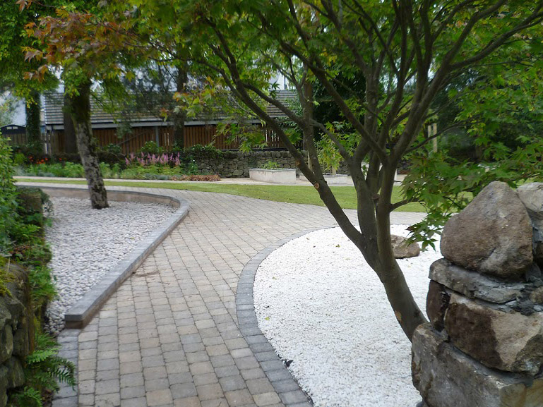 Showing smooth cobbled path curving past Japanese gravel planting bed