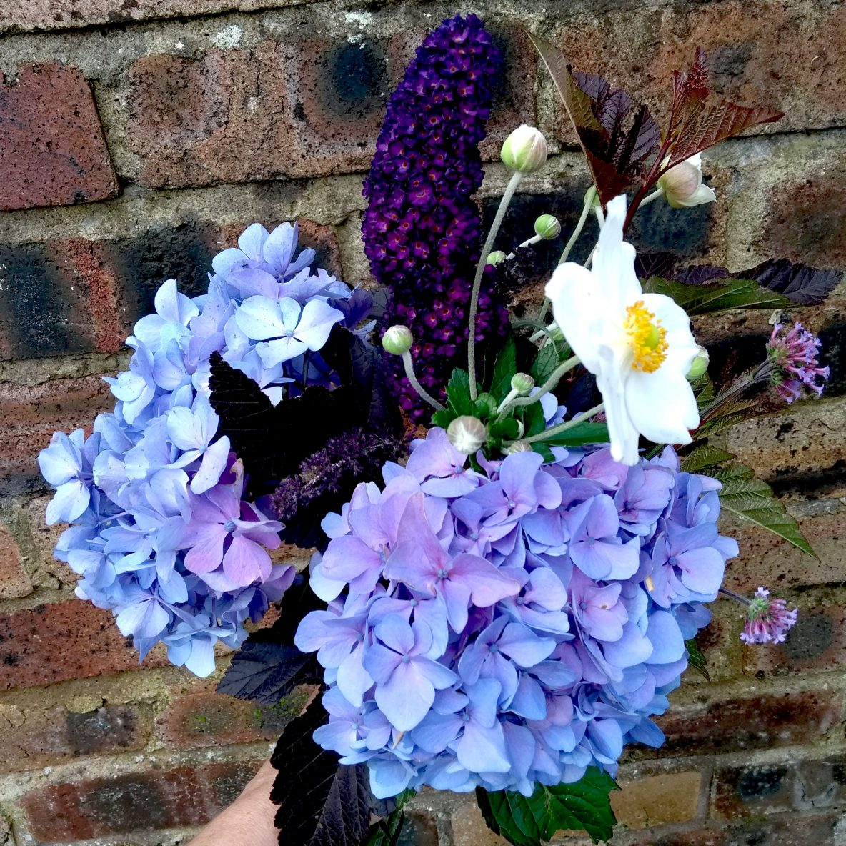 Blue hydrangea, purple buddleia and white anemone posy against a brick wall