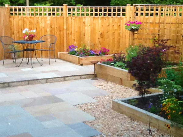 Indian sandstone paving sparkles beside timber raised beds. Bistro table and chairs at far end on sunny raised terrace